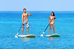 Stand up paddleboard beach people on paddle board. Stand up paddleboarding beach people on stand up paddle board, SUP surfboard surfing in ocean sea on Big Royalty Free Stock Image