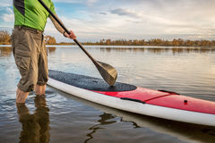 Stand up paddleboard on lake. Male paddler is starting paddling workout on his stand up paddleboard on a lake in Colorado Stock Photo