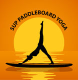 Stand up paddleboard Yoga. Woman silhouette in downwards facing dog leg air pose Royalty Free Stock Photo