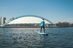 Stand up paddleboarding. Girl with a paddle, standing on the Board, sup surfing on the river at background of city stock photos