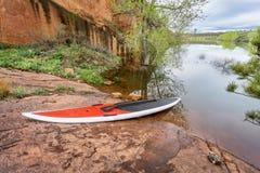 Stand up paddleborad on lake shore Stock Photos