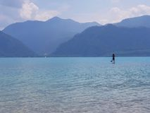 Stand up paddler on a clear blue moutain lake in Austria royalty free stock images