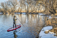 Stand up paddler poling on shallow river. Cache la Poudre River in Colorado winter scenery Stock Photo