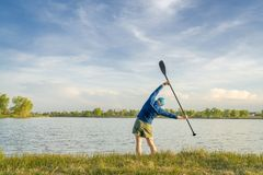 Stand up paddler is stretching and warming up stock photos