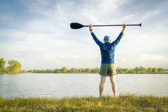 Stand up paddler is stretching and warming up stock image