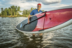 Stand up paddling in Colorado. Senior male with hist stand up paddleboard on a lake in Colorado Stock Image
