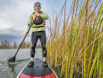 Stand up paddling in Colorado. Senior paddler in life jacket enjoying stand up paddling on lake, fall scenery with cattail in Fort Collins, Colorado Stock Image