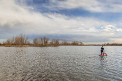 Stand up paddling in fall. A calm lake in late fall scenery with a lonely male stand up paddler Royalty Free Stock Photos