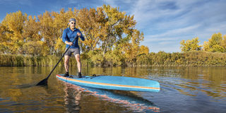 Stand up paddling in fall colors Stock Image