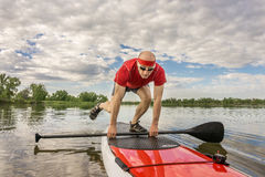 Stand up paddling on a lake in Colorado. Senior male paddler starting his workout on a stand up paddleboard - a local lake in Colorado under cloudy sky Stock Photos