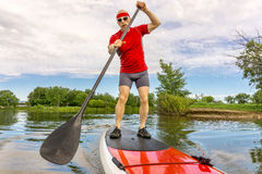 Stand up paddling on a lake in Colorado. Senior muscular male paddler enjoying paddling stand up paddleboard on a local lake in Fort Collins, Colorado Stock Photo