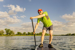 Stand up paddling on lake in Colorado. Senior muscular male paddler enjoying paddling stand up paddleboard on a local lake in Fort Collins, Colorado Royalty Free Stock Images