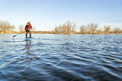 Stand up paddling on a lake in Colorado. Winter or early spring scenery Royalty Free Stock Photo