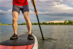 Stand up paddling on lake. Legs of muscular male paddler on a stand up paddleboard - a calm lake in summer Royalty Free Stock Photo