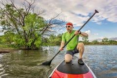 Stand up paddling on lake. Senior male paddler kneeling on his stand up paddleboard, a local lake in Colorado Stock Photo