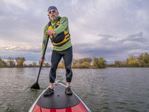 Stand up paddling on a lake. Senior paddler in life jacket enjoying stand up paddling on lake, fall scenery in Fort Collins, Colorado Royalty Free Stock Image