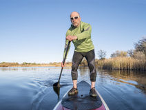 Stand up paddling on a lake. Senior paddler in life jacket enjoying stand up paddling on lake, fall scenery in Fort Collins, Colorado Royalty Free Stock Photos