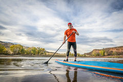 Stand up paddling on mountain lake Stock Photos