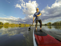 Stand up paddling. Senior male paddler enjoying workout on stand up paddleboard (SUP), calm lake in Colorado, summer Stock Photography