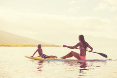 Stand Up Paddling at Sunrise. Mother and son stand up paddling at sunrise, Summer fun outdoor lifestyle Stock Photography
