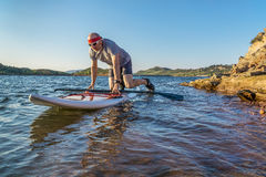 Stand up paddling (SUP) in Colorado. Male paddler starting stand up paddling on a rocky shore of Horsetooth Reservoir, Fort Collins, Colorado, summer scenery Stock Image