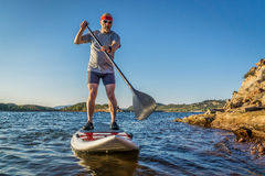 Stand up paddling (SUP) in Colorado. Senior male paddler enjoying stand up paddling on a sunny summer day - Horsetooth Reservoir, Fort Collins, Colorado Stock Photography