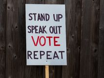 Stand up speak out vote repeat sign. Against a wood fence stock photography