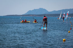 Stand up Surfer Man Paddleboarding on Board among Canoes and Win Stock Images