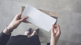 Stand up woman holding white folded a4 paper and brown envelope Royalty Free Stock Photography