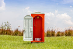 Standalone of red toilet with white door open contrast with gree. N grass and tree in the meadow and clear blue sky Royalty Free Stock Images