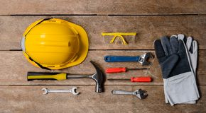 Standard construction safety equipment and tools set on wooden t. Standard construction safety equipment and tools set on old wooden background. top view, safety stock photography