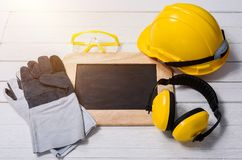 Standard construction safety equipment on wooden table Royalty Free Stock Images