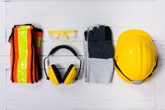 Standard construction safety equipment on wooden table. top view. Standard construction safety equipment on white wooden background. top view, safety first stock photos