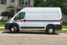 Standard delivery truck makes a delivery to home Royalty Free Stock Images