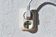 Standard electric socket. Closeup of a standard electric socket and a plugged cable in it stock photos