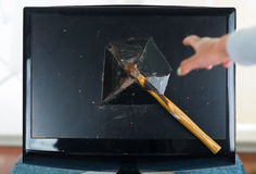 Standard hammer stuck in computer screen after Royalty Free Stock Photography