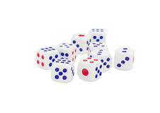 Standard plastic six-sided dice with rounded corners. Standard plastic white six-sided dice with with red and blue dots and rounded corners on a light background Royalty Free Stock Photography