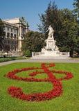 Standbeeld van Amadeus Mozart met bloembedden als g-sleutel in Burg Stock Afbeeldingen