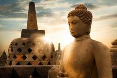 Standbeeld van Boedha tegen de achtergrond van de zonsopgang met stralen van licht in de Borobudur-Tempel Java Island indonesië b royalty-vrije stock fotografie