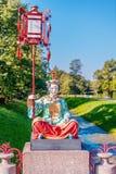 Standbeeld van de Chinese vrouwenzitting op een voetstuk met een grote lamp op een pool Stock Afbeelding