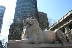 Standbeeld van een leeuw op cityscape achtergrond Stock Foto's