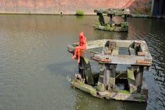 Standbeeld van een rode vrouwenzitting op een ponton Stock Foto