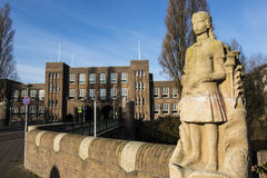 Standbeeld van een schoolmeisje en de voorgevel van Lyceum van Amsterdam een middelbare school in het Zuiden van Amsterdam, Holla stock afbeeldingen