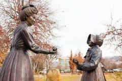 Standbeeld van een vrouw die een meisje een appel in Boise Rose Garden overhandigen stock afbeeldingen