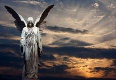 Standbeeld van engel en zonsondergang Stock Afbeeldingen