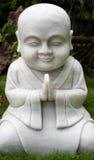 Standbeeld van het glimlachen monnik het bidden Stock Afbeeldingen