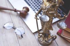Standbeeld van rechtvaardigheid, rechtershamer en laptop stock foto's