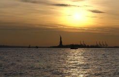 Standbeeld van Vrijheid en zonsondergang stock foto
