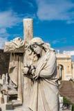 Standbeeld van vrouwen die een kruis koesteren Stock Afbeelding