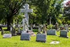 Standbeelden, Kruisen, en Grafstenen in een Begraafplaats Stock Foto